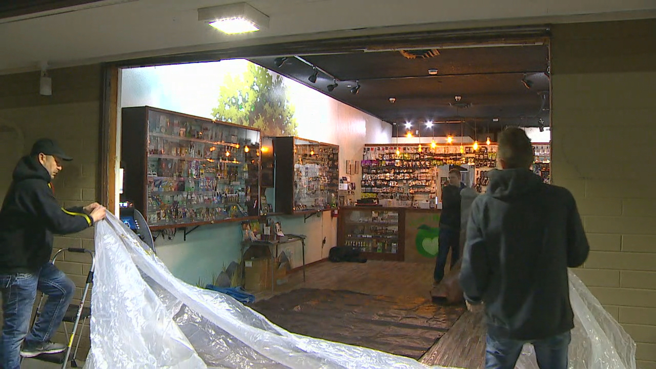 Employees prepare to cover the front of the store with plastic sheeting after a car crashed through the entrance. (KOMO photo)<p></p>