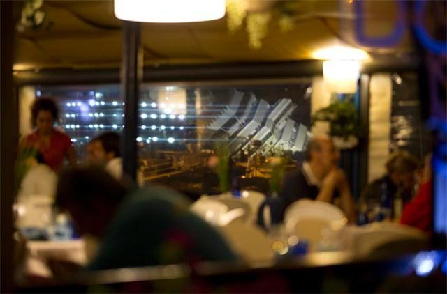 The Costa Concordia ship is sen through the windows of a sea front restaurant as it lies on its side on the Tuscan Island of Giglio, Italy, Monday, Sept. 16, 2013.